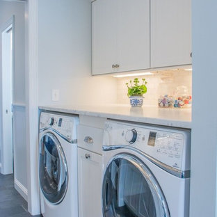 This is an example of a small traditional galley utility room in Cleveland with a drop-in sink, white cabinets, white walls, a side-by-side washer and dryer and grey floor.