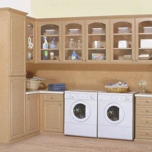 Klassisk inredning av en mellanstor parallell tvättstuga enbart för tvätt, med luckor med glaspanel, skåp i mellenmörkt trä, vita väggar, mellanmörkt trägolv, en tvättmaskin och torktumlare bredvid varandra och brunt golv