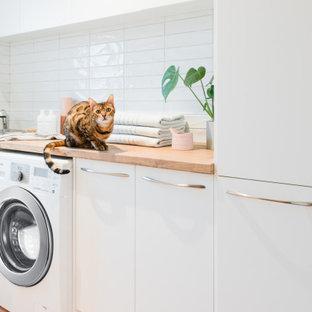 Immagine di una sala lavanderia scandinava di medie dimensioni con lavello da incasso, nessun'anta, ante bianche, top in laminato, pareti bianche, pavimento in terracotta e lavatrice e asciugatrice affiancate