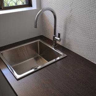Idee per una piccola sala lavanderia moderna con lavello da incasso, ante a persiana, ante bianche, top in quarzo composito, pareti bianche, pavimento in gres porcellanato, lavatrice e asciugatrice affiancate e pavimento bianco