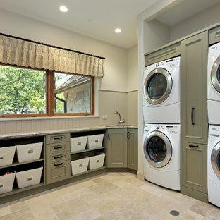 Ejemplo de lavadero tradicional con puertas de armario verdes, lavadora y secadora apiladas, suelo beige y encimeras beige