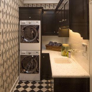 Immagine di una piccola sala lavanderia tradizionale con ante nere, lavatrice e asciugatrice a colonna, lavello sottopiano, ante in stile shaker, pareti multicolore, pavimento multicolore e top bianco