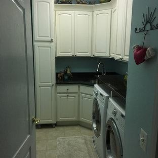 Immagine di una sala lavanderia classica di medie dimensioni con ante bianche, lavello sottopiano, ante con bugna sagomata, top in superficie solida, pareti blu, pavimento in gres porcellanato, lavatrice e asciugatrice affiancate, pavimento beige e top nero