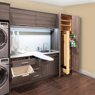 Foto di una lavanderia multiuso design di medie dimensioni con ante lisce, pareti beige, lavatrice e asciugatrice a colonna e ante grigie