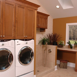 Transitional single-wall linoleum floor utility room photo in Cincinnati with medium tone wood cabinets, laminate countertops, a side-by-side washer/dryer, shaker cabinets and brown walls