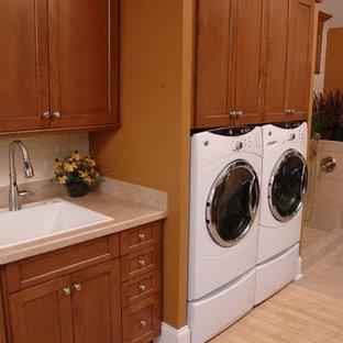 Exempel på ett klassiskt l-format grovkök, med en nedsänkt diskho, skåp i mellenmörkt trä, laminatbänkskiva, orange väggar, linoleumgolv, en tvättmaskin och torktumlare bredvid varandra och skåp i shakerstil
