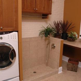 Foto på ett vintage linjärt grovkök, med en nedsänkt diskho, luckor med infälld panel, skåp i mellenmörkt trä, laminatbänkskiva, linoleumgolv, en tvättmaskin och torktumlare bredvid varandra och bruna väggar