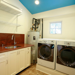 Mid-sized elegant travertine floor dedicated laundry room photo in Tampa with an undermount sink, white cabinets, granite countertops, white walls and a side-by-side washer/dryer