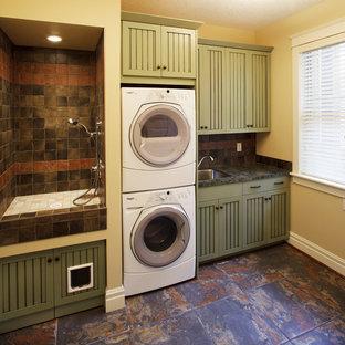 Foto di una piccola lavanderia multiuso eclettica con lavello da incasso, ante con riquadro incassato, ante verdi, top in laminato, pareti beige, pavimento in ardesia e lavatrice e asciugatrice a colonna