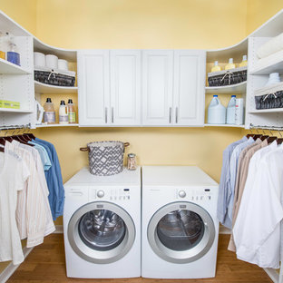 Large traditional u-shaped separated utility room in Other with raised-panel cabinets, white cabinets, yellow walls, medium hardwood flooring, a side by side washer and dryer and brown floors.
