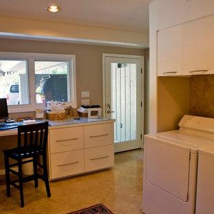 Idee per una grande lavanderia multiuso minimalista con ante lisce, ante bianche, top in vetro, pareti beige, pavimento in travertino e lavatrice e asciugatrice affiancate