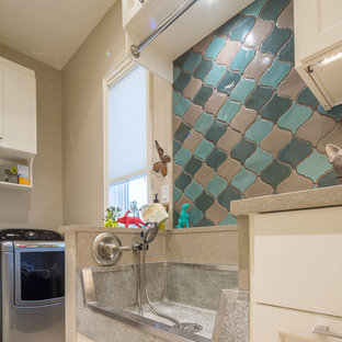 Large modern galley utility room in Austin with an utility sink, shaker cabinets, white cabinets, engineered stone countertops, beige walls and a side by side washer and dryer.
