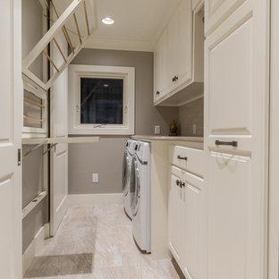 Exempel på ett mellanstort klassiskt linjärt grovkök, med luckor med upphöjd panel, vita skåp, granitbänkskiva, beige väggar, klinkergolv i porslin och en tvättmaskin och torktumlare bredvid varandra