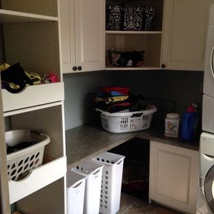 Immagine di una sala lavanderia chic di medie dimensioni con ante con bugna sagomata, ante bianche, top in laminato, pareti grigie, pavimento in linoleum e lavatrice e asciugatrice a colonna