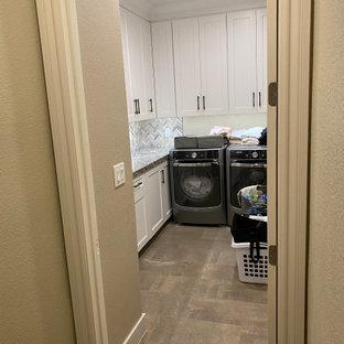 Inspiration för en mellanstor funkis grå l-formad grått tvättstuga enbart för tvätt, med en enkel diskho, luckor med profilerade fronter, vita skåp, granitbänkskiva, grått stänkskydd, stänkskydd i cementkakel, beige väggar, klinkergolv i keramik, en tvättmaskin och torktumlare bredvid varandra och beiget golv