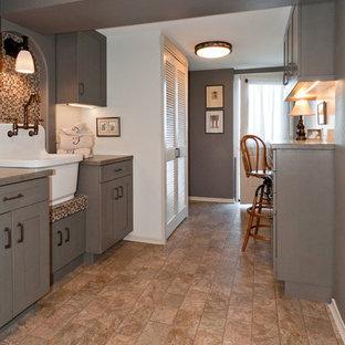Immagine di una piccola lavanderia multiuso american style con lavello stile country, ante in stile shaker, ante grigie, top in laminato, pareti grigie, pavimento in vinile e lavatrice e asciugatrice a colonna