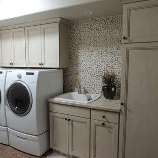 Inspiration för en mellanstor vintage linjär tvättstuga enbart för tvätt, med en nedsänkt diskho, luckor med infälld panel, skåp i ljust trä, laminatbänkskiva, vita väggar, linoleumgolv, en tvättmaskin och torktumlare bredvid varandra och beiget golv