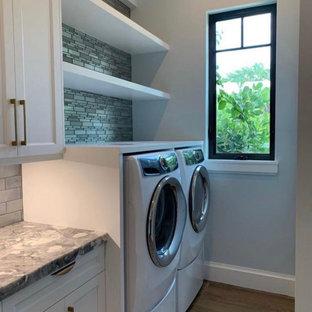 Inspiration för mellanstora moderna parallella flerfärgat grovkök, med en nedsänkt diskho, vita skåp, marmorbänkskiva, grått stänkskydd, grå väggar, målat trägolv, en tvättmaskin och torktumlare bredvid varandra och flerfärgat golv