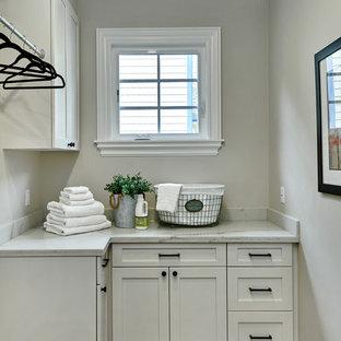 Idéer för att renovera en liten medelhavsstil vita l-formad vitt tvättstuga enbart för tvätt, med skåp i shakerstil, vita skåp, bänkskiva i kvarts, grå väggar, klinkergolv i porslin, en tvättmaskin och torktumlare bredvid varandra och rött golv