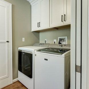 Idée de décoration pour une petit buanderie linéaire tradition avec un placard, un sol en bois clair, des machines côte à côte, un sol marron, un placard à porte shaker, des portes de placard blanches et un mur gris.