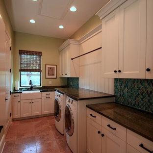 Foto di un'ampia sala lavanderia mediterranea con lavello stile country, ante bianche, top in granito, pareti verdi, pavimento in terracotta, lavatrice e asciugatrice affiancate, ante con riquadro incassato e pavimento marrone