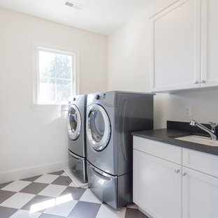 Photo of a classic single-wall separated utility room in DC Metro with a submerged sink, white cabinets, white walls, a side by side washer and dryer, multi-coloured floors and black worktops.