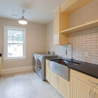 Foto di una sala lavanderia country con lavello stile country, ante a filo, ante gialle, pareti beige, lavatrice e asciugatrice affiancate, pavimento beige e top nero