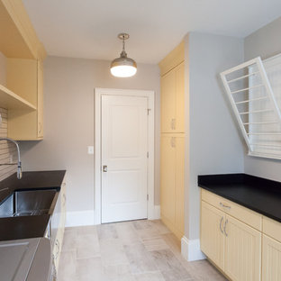 Photo of a rural galley separated utility room in DC Metro with a belfast sink, beaded cabinets, yellow cabinets, beige walls, a side by side washer and dryer, beige floors and black worktops.