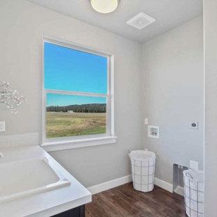 Bild på en mycket stor amerikansk vita vitt tvättstuga enbart för tvätt, med en allbänk, skåp i shakerstil, laminatbänkskiva, vitt stänkskydd, stänkskydd i cementkakel, grå väggar, laminatgolv, en tvättmaskin och torktumlare bredvid varandra och brunt golv