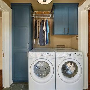 Exempel på en liten amerikansk linjär tvättstuga enbart för tvätt, med skåp i shakerstil, blå skåp, skiffergolv, en tvättmaskin och torktumlare bredvid varandra, grått golv och bruna väggar
