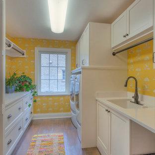 Foto di una lavanderia multiuso shabby-chic style di medie dimensioni con lavello sottopiano, ante in stile shaker, ante bianche, pareti gialle, pavimento con piastrelle in ceramica e lavatrice e asciugatrice affiancate