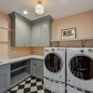 Immagine di una piccola sala lavanderia classica con lavello sottopiano, ante a filo, ante blu, top in quarzo composito, pareti rosa, pavimento con piastrelle in ceramica, lavatrice e asciugatrice affiancate, pavimento nero e top bianco