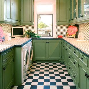 Medelhavsstil inredning av en u-formad tvättstuga enbart för tvätt, med gröna skåp, en tvättmaskin och torktumlare bredvid varandra, luckor med infälld panel, kaklad bänkskiva och flerfärgat golv