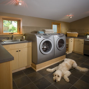 Inspiration for a large contemporary u-shaped travertine floor and gray floor dedicated laundry room remodel in Minneapolis with light wood cabinets, a drop-in sink, flat-panel cabinets, solid surface countertops, beige walls, a side-by-side washer/dryer and gray countertops