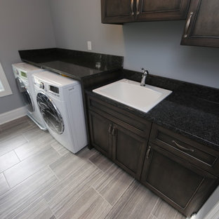 Medium sized traditional single-wall separated utility room in Chicago with a built-in sink, granite worktops, grey walls, porcelain flooring, a side by side washer and dryer, grey floors, black worktops, recessed-panel cabinets and dark wood cabinets.