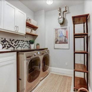Inspiration för en mellanstor vintage bruna parallell brunt tvättstuga enbart för tvätt, med en nedsänkt diskho, luckor med infälld panel, vita skåp, bänkskiva i kvarts, flerfärgad stänkskydd, stänkskydd i mosaik, grå väggar, ljust trägolv och en tvättmaskin och torktumlare bredvid varandra