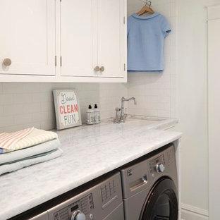Exempel på en liten minimalistisk parallell tvättstuga enbart för tvätt, med en nedsänkt diskho, luckor med infälld panel, vita skåp, marmorbänkskiva, vita väggar, klinkergolv i porslin och en tvättmaskin och torktumlare bredvid varandra