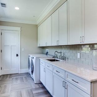 Bild på en stor amerikansk parallell tvättstuga enbart för tvätt, med en nedsänkt diskho, skåp i shakerstil, vita skåp, bänkskiva i kvarts, beige väggar, klinkergolv i keramik och en tvättmaskin och torktumlare bredvid varandra