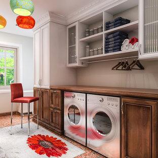 Immagine di una lavanderia multiuso tradizionale di medie dimensioni con top in legno, pavimento in linoleum, lavatrice e asciugatrice affiancate, pavimento arancione, ante con riquadro incassato, ante in legno bruno e pareti grigie