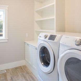 Bild på en mellanstor maritim tvättstuga enbart för tvätt, med öppna hyllor, vita skåp, träbänkskiva, beige väggar och en tvättmaskin och torktumlare bredvid varandra