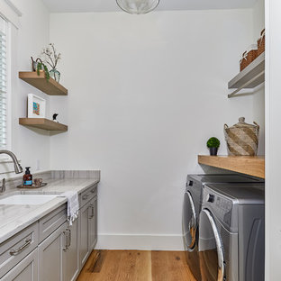 Large nautical separated utility room in Charleston with a submerged sink, recessed-panel cabinets, grey cabinets, white walls, light hardwood flooring, a side by side washer and dryer, grey worktops and quartz worktops.