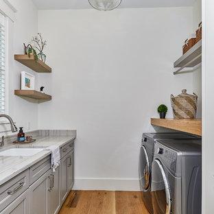 Ispirazione per una grande sala lavanderia costiera con lavello sottopiano, ante con riquadro incassato, ante grigie, pareti bianche, parquet chiaro, lavatrice e asciugatrice affiancate, top grigio e top in quarzite