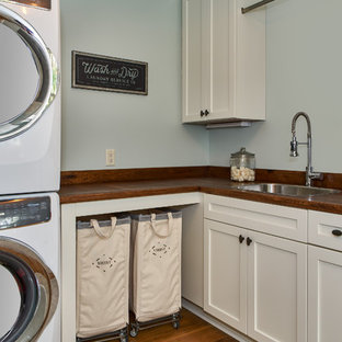Inspiration for a large coastal l-shaped utility room in Charleston with a built-in sink, white cabinets, wood worktops, medium hardwood flooring, a stacked washer and dryer, brown floors, brown worktops and green walls.