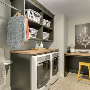 This is an example of a large traditional l-shaped utility room in Minneapolis with an utility sink, open cabinets, grey cabinets, laminate countertops, grey walls, ceramic flooring, a side by side washer and dryer and grey floors.