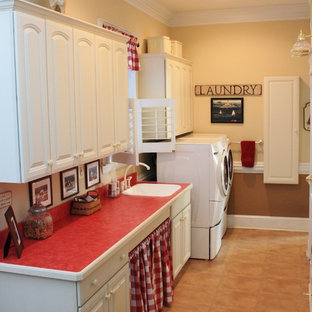 Photo of a large rural single-wall separated utility room in DC Metro with raised-panel cabinets, white cabinets, beige walls, a side by side washer and dryer, a built-in sink, laminate floors and red worktops.