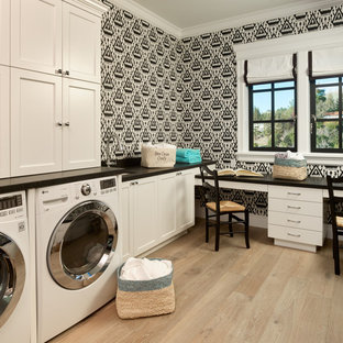 This is an example of a classic l-shaped utility room in San Francisco with white cabinets, granite worktops, light hardwood flooring, a side by side washer and dryer, multi-coloured walls, black worktops and recessed-panel cabinets.