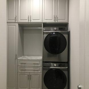 Foto på en liten funkis flerfärgade linjär tvättstuga enbart för tvätt, med luckor med upphöjd panel, grå skåp, laminatbänkskiva, grå väggar, klinkergolv i porslin och en tvättpelare