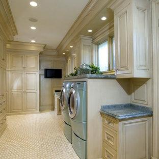 Inredning av en klassisk stor blå u-formad blått tvättstuga enbart för tvätt, med vita skåp, beiget golv, luckor med upphöjd panel, granitbänkskiva, beige väggar, klinkergolv i porslin och en tvättmaskin och torktumlare bredvid varandra
