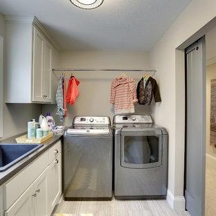Inredning av en klassisk stor l-formad tvättstuga enbart för tvätt, med en nedsänkt diskho, skåp i shakerstil, vita skåp, laminatbänkskiva, beige väggar, klinkergolv i keramik och en tvättmaskin och torktumlare bredvid varandra