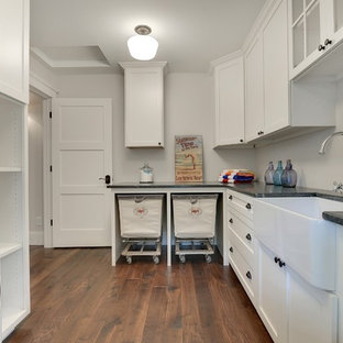 Inspiration for a large transitional l-shaped dark wood floor and brown floor dedicated laundry room remodel in Minneapolis with a farmhouse sink, recessed-panel cabinets, white cabinets, soapstone countertops, gray walls and a stacked washer/dryer